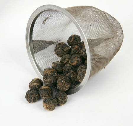 Tea balls in a diffuser, isolated. photo