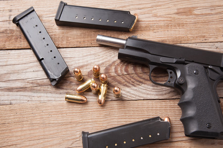 A 1911 45 caliber pistol with bullets. photo