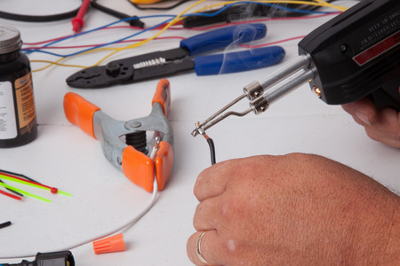 soldering: A person soldering wires together.