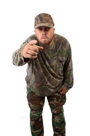 A man in camouflage, pointing, isolated on a white background.  Stock Photo