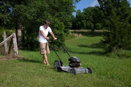 Mowing the grass with a lawnmower.
