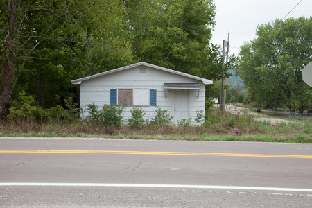 boarded: A small white house with a boarded up window.