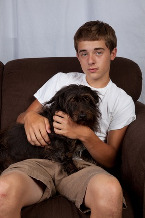 couch potato: A teenage boy sitting on a couch with a dog.