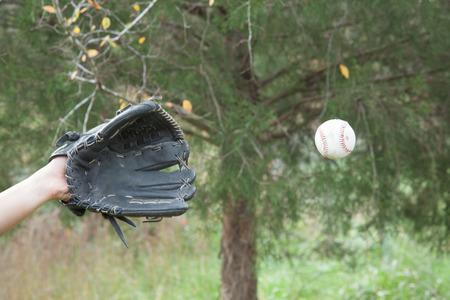 guante de beisbol: Alguien con un guante de b�isbol negro prepar�ndose para atrapar una pelota de b�isbol Foto de archivo