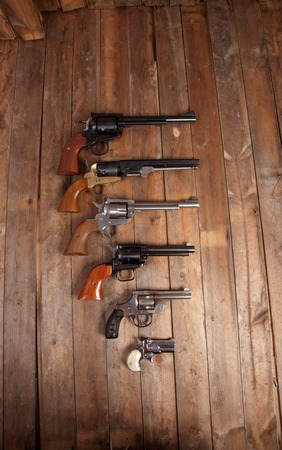pistols: A group of pistols on a wooden background. Stock Photo