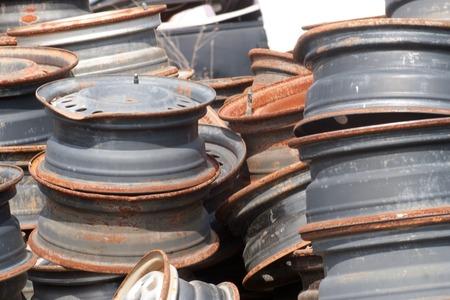 salvage yard: Rusty wheels stacked at a junkyard.