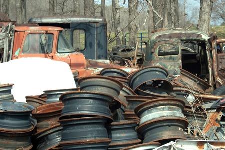 salvage yard: Trucks and wheels at a junkyard.