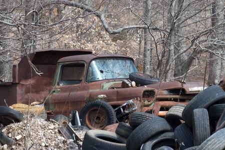 junkyard: An old truck and tires in a junkyard. Stock Photo