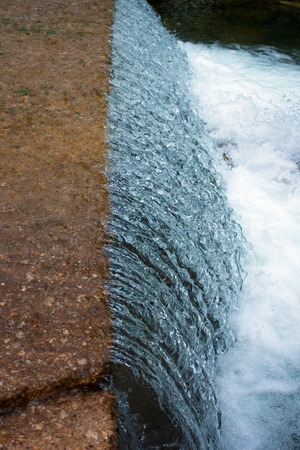 crack: A close up of water flowing over a concrete bridge. Stock Photo