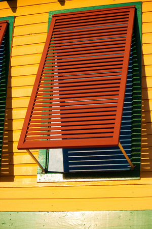 shutter: A red shutter on a yellow wall.