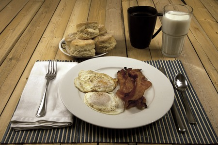 bacon and eggs: A breakfast of bacon, eggs, and biscuits.