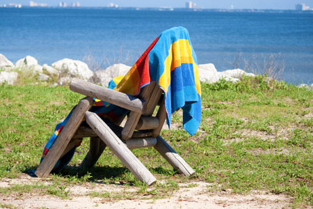 beach towel: A beach towel hanging on a wooden chair.