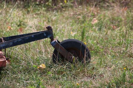bush hog: The wheel of a brush hog in grass.