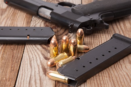 A pistol with two clips and bullets. Stock Photo
