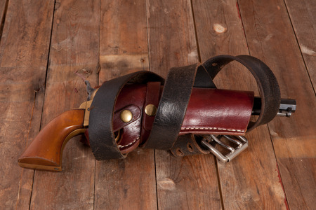 holster: A revolver in a holster on a wooden background. Stock Photo