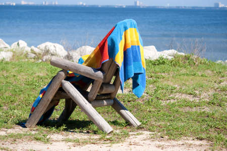 beach towel: A beach towel drying on the back of a chair.