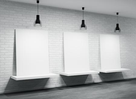 three shelves: Three posters on the white brick wall Stock Photo