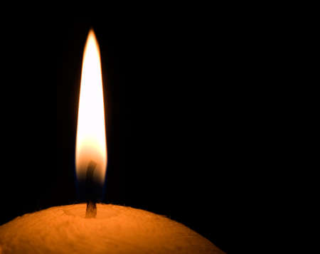 Burning candle isolated on a black background. photo