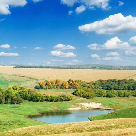 Lago, campo verde y cielo azul