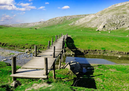foot bridge: The wooden foot bridge and old mountains Stock Photo