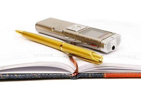 dictating: Dict�fono, el Bloc de notas y bol�grafo sobre fondo blanco Foto de archivo