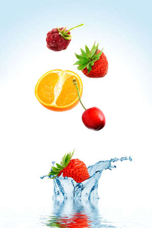Fruit falling in water on a white background Stock Photo
