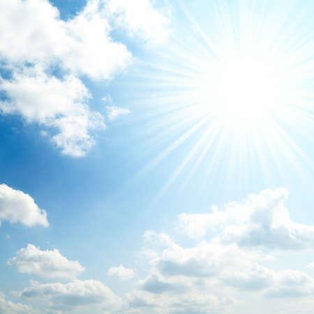 fluffy clouds: sun on blue sky   Stock Photo