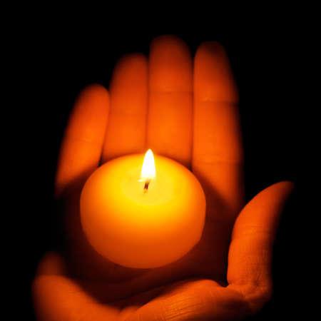 kerzen: Brennende Kerze in der Hand.