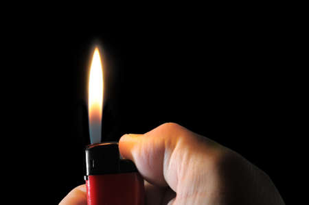 lighter in hand isolated on a black                                     photo