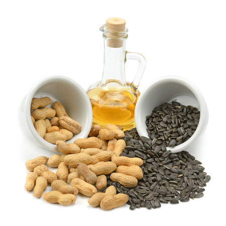 Sunflower seeds, peanuts and oil isolated on a white background                                     Stock Photo