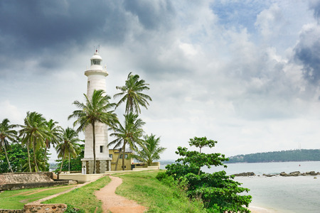 galle: Lighthouse and palm trees on background sky.