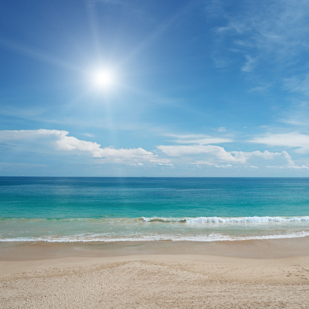 sunny beach: Sandy beach and sun in blue sky Stock Photo