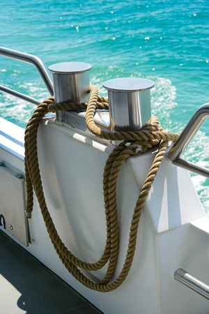 coiled rope: bollard with coiled rope on board ship