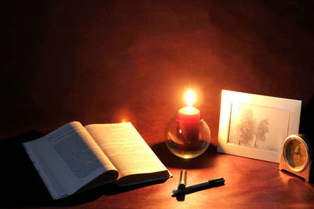 Meditations, exposed book and burning candle photo