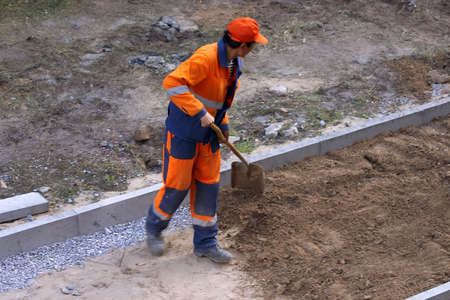 pile engine: a worker with a shovel throws building material