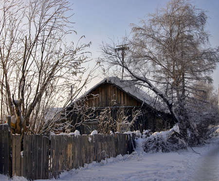 snow-capped log cabin in surroundings trees and fence on a background clear sky photo