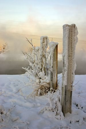 blasted: winter misty landscape on the river with the snow-bound blasted fence