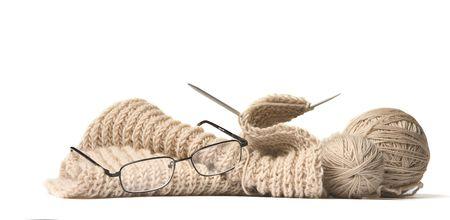gomitoli di lana: Raggi, bicchieri, lana palla, e non finito di maglieria su sfondo bianco