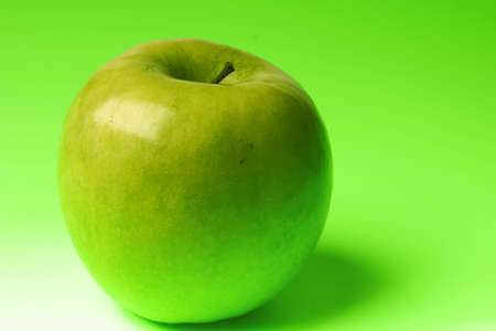 appetizing apple of green color on a brightly green background photo