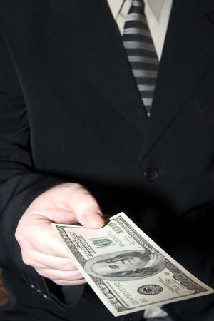 one hundred dollars: a young businessman in a suit and tie holds one hundred dollars in a hand