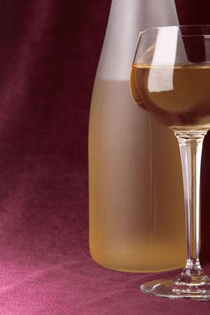 claret: white wine in glass and bottle on a claret background