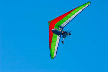 soaring a motorized hang-glider on a background blue sky photo