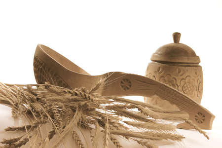 goldish: wooden tableware for preparation and goldish stems and corns of ripe cereal culture squeak on a white background