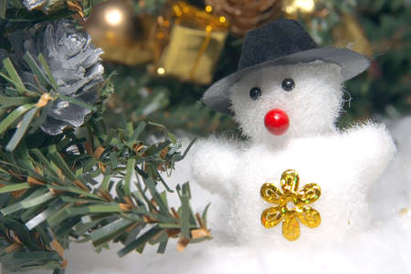 snowdrifts: cute snowman to a dark hat in an environment of snowdrifts and christmas evergreen trees