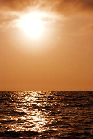 Beautiful sunset above a surface of dark sea waves photo