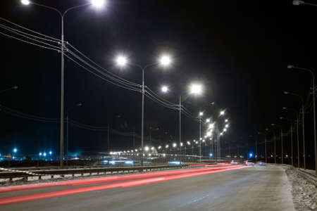 shined: Night street with traces from light of headlights shined with street lanterns Stock Photo