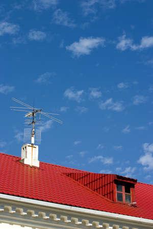 dormer: brillantes de color rojo con techo buhardilla sobre un fondo azul cielo Foto de archivo