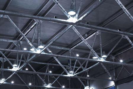bedrijfshal: krachtige lampen en metalen buizen onder plafond van industrieel gebouw