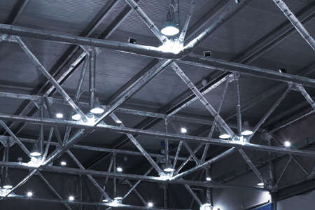 ceiling lamps: powerful lamps and metallic pipes under ceiling of industrial building Stock Photo