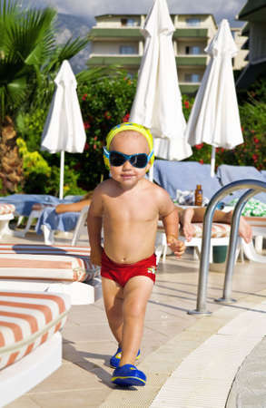 cowards: baby boy in fashionable glasses and in red swimming cowards running along a pool